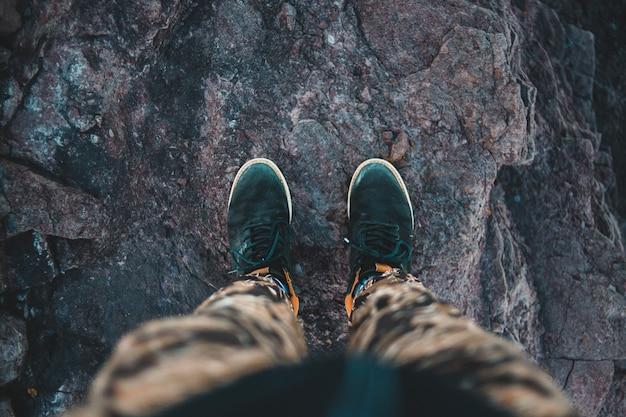 茶色の岩の上に立っている黒と白のスニーカーの人