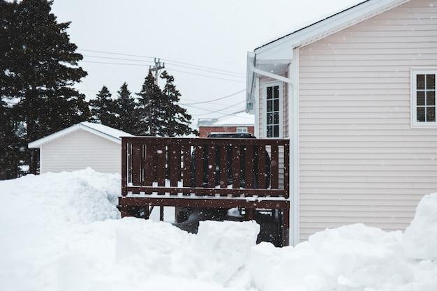 昼間に緑の木の近くの白い木造住宅