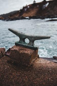 昼間の海の近くの茶色の岩の上の茶色の金属アンカー