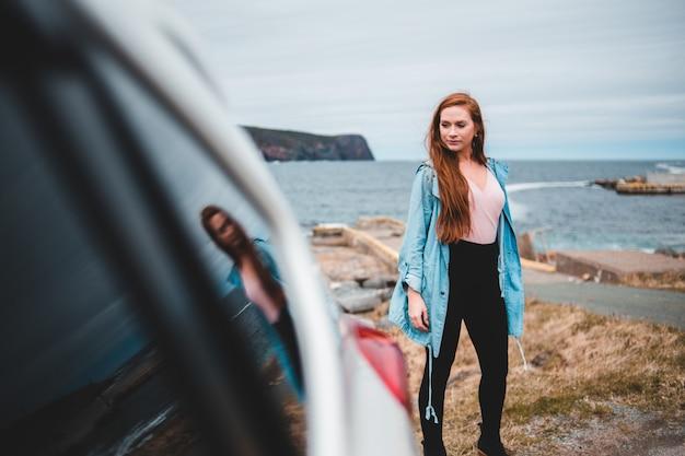 車の横に立っている青いジャケットの女性