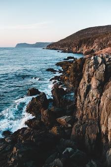 昼間の海の横にある茶色のロッキーマウンテン