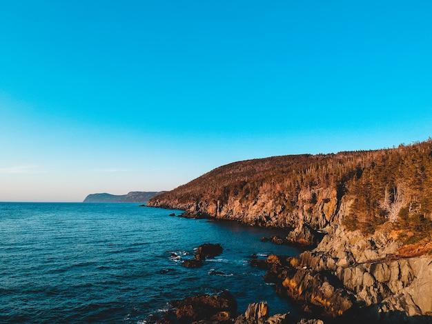 Коричневая скалистая гора около голубого моря под голубым небом в дневное время