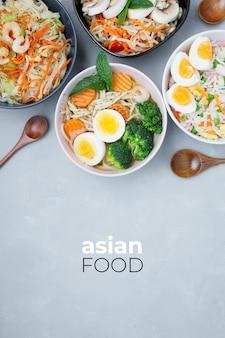 Вкусная и полезная азиатская еда на сером текстурированном фоне