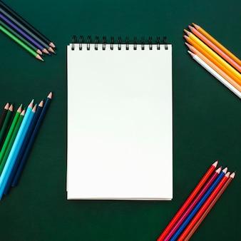 緑のボードに色鉛筆でノートブック、学校に戻ってのための美しいフラットなレイアウトの構成