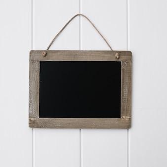 モックアップのための白い木ボード上の美しい空の黒板