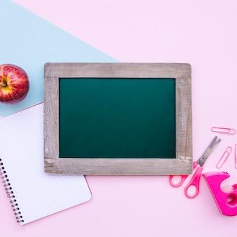 ライトブルーとピンクの背景に模擬のための緑のスレートと学校の構成に戻って