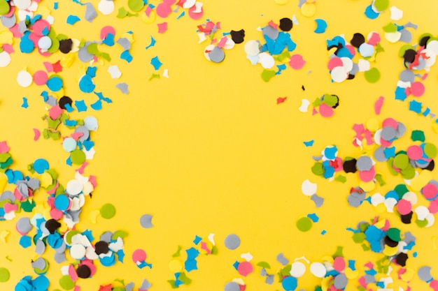 Конфетти на желтом фоне после окончания вечеринки