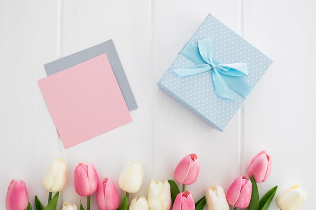 グリーティングカードと母の日の白い木製の背景上のチューリップと青いギフト