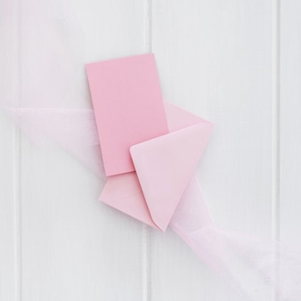 白い木製の背景上の封筒とピンクのグリーティングカード