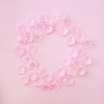 ピンクの背景にピンクのバラの花びらで作られたフレーム