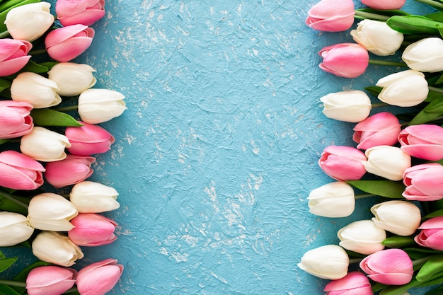 青いグランジ背景にピンクと白のチューリップ