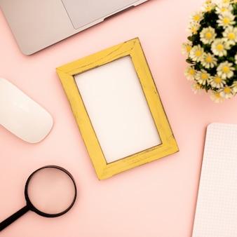 ピンクの背景のモックアップのための空白のフォトフレーム付きデスク