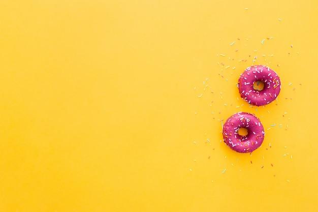 黄色の背景にピンクのアイシングでドーナツのトップビュー