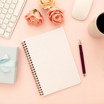 ピンクのバラ、コーヒーカップ、空白のスパイラルノート、ペンを持つデスクテーブル。平面図、平干し