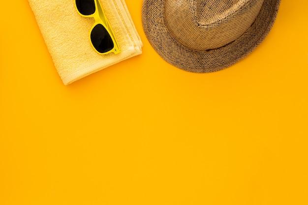 黄色の背景にビーチアクセサリー。サングラス、タオル。フリップフロップと縞模様の帽子。