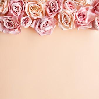 花の組成パステル調のピンクの背景にピンクのバラの花。フラットレイアウト、上面図、コピースペース