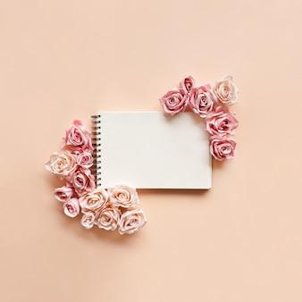 ピンクのバラは明るいピンクの背景のノートブックの周りに並んでいます。