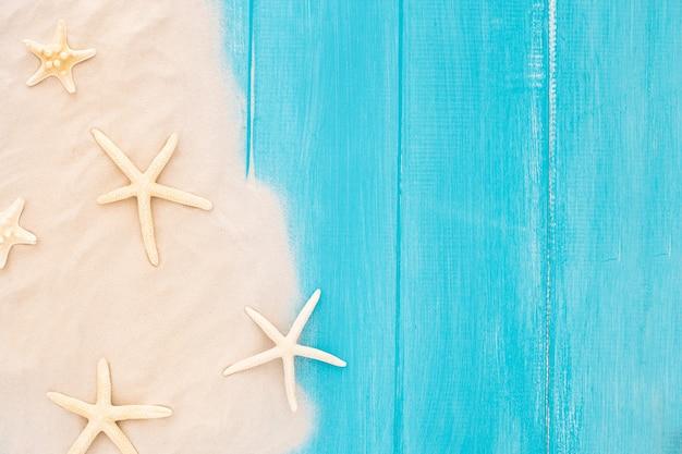 青い木製の背景に砂と美しいヒトデ