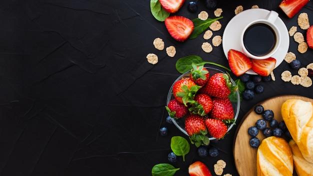 黒い木製の背景に健康的な朝食。上面図。テキスト用の空き容量