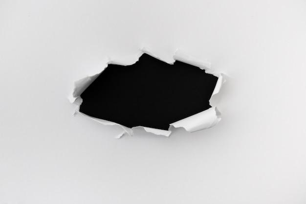 黒革の背景上のテキスト用のスペースと引き裂かれた紙