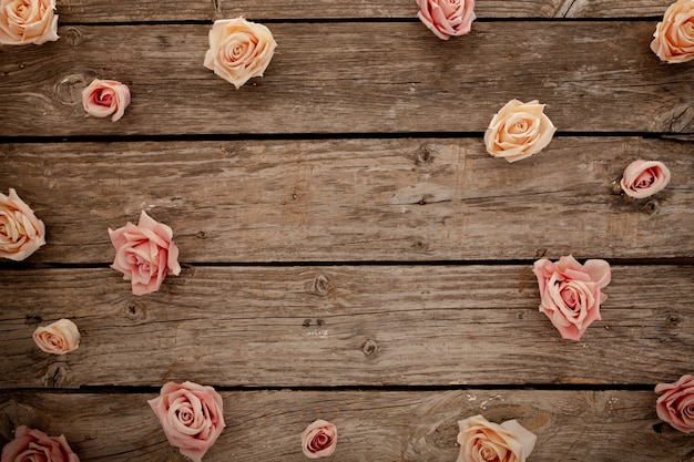 茶色の木製の背景にピンクのバラ