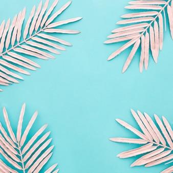 青の背景にピンクのヤシの美しい構図の葉します。