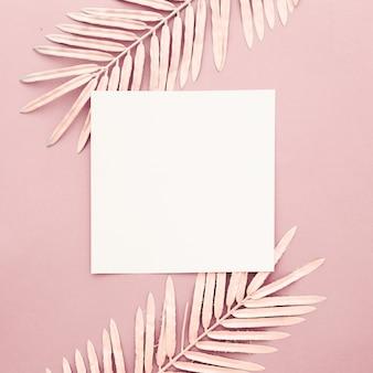 ピンクの背景に空白のフレームとピンクのヤシの葉