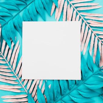 青色の背景にピンクとブルーのヤシの葉を持つ空白の紙