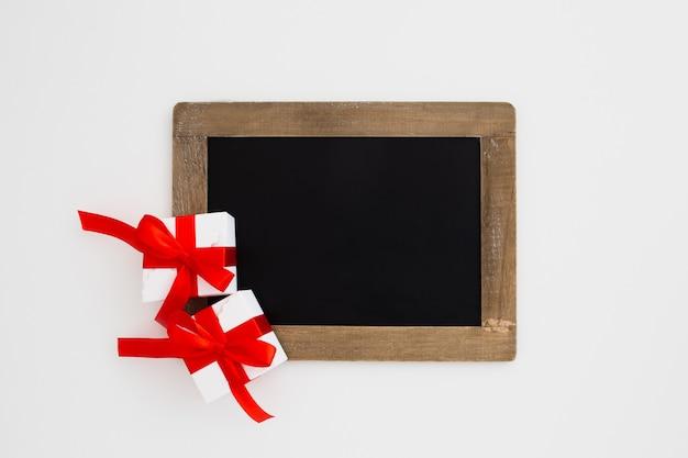 白い背景の上のクリスマスプレゼントと黒板