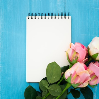 Красивая композиция с блокнотом и розами на синем деревянном