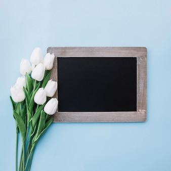 青い背景に白いチューリップとモックアップのための美しい黒板