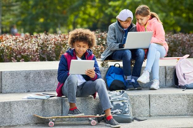 Дети, использующие гаджеты на открытом воздухе