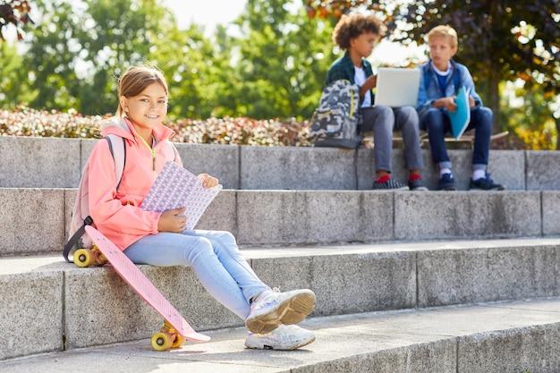 スケートボードと本を持つ少女