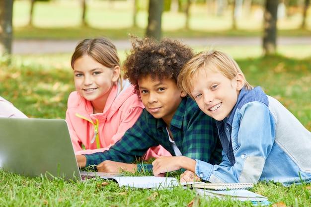 Дети используют ноутбук на открытом воздухе