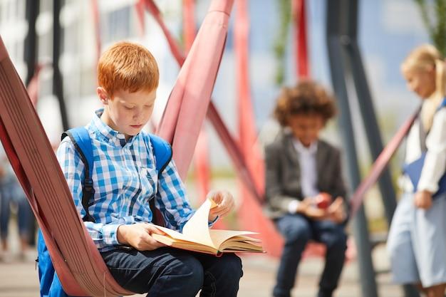 屋外で本を読む少年