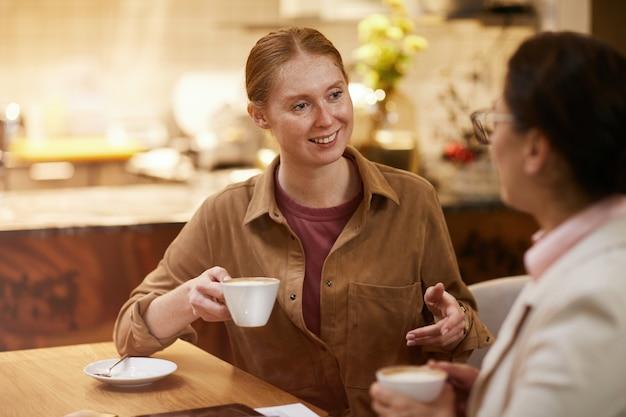 Друзья пьют кофе в кафе