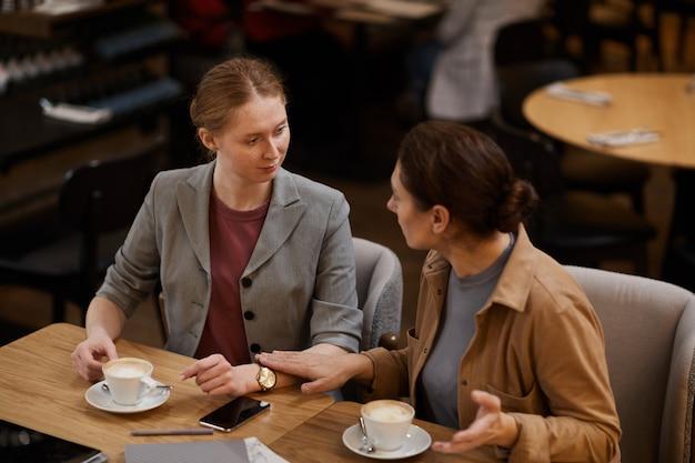 Две девушки пьют кофе в кафе