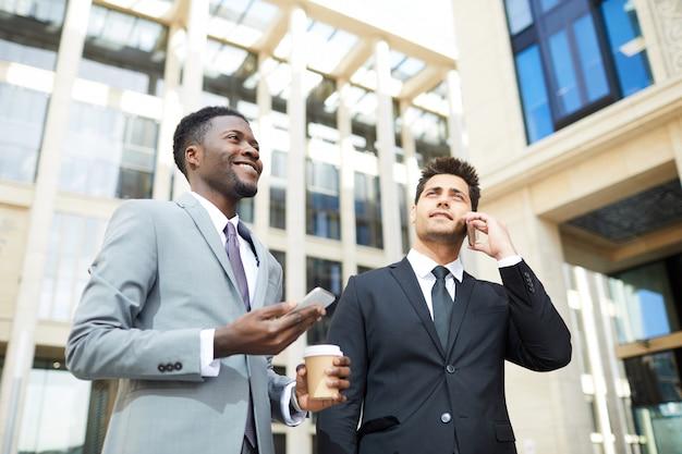 Два менеджера используют телефоны на улице