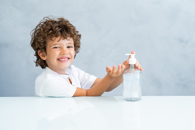手の消毒剤を使用している子供