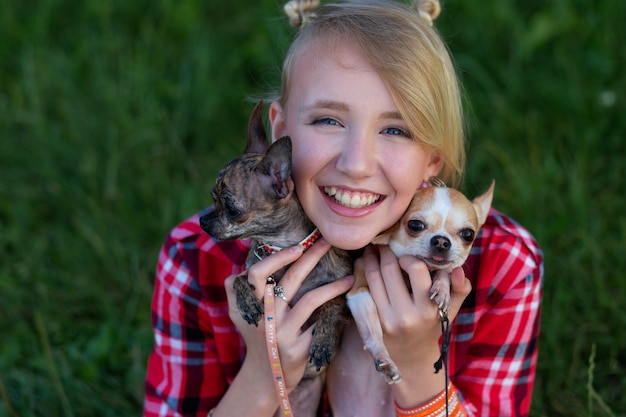 Молодая девушка в красной рубашке с двумя собаками на руках