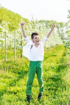 Мальчик в цветущем саду прыгает