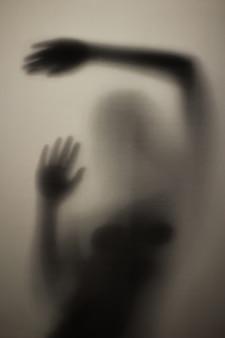 Страшный силуэт девушки за стеклом в ванной комнате на свету