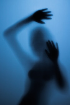 Страшный силуэт девушки за стеклом в ванной комнате. страшная девушка за стеклянной дверью в синем свете