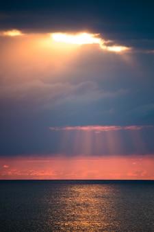 Увлекательный морской пейзаж с драматическими облаками и солнечным светом между ними