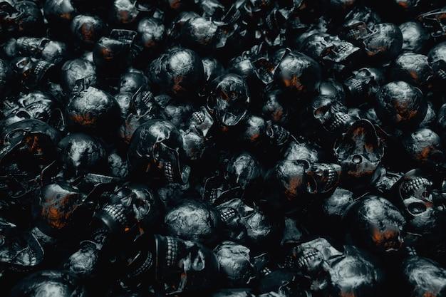 黒いテクスチャの人間の頭蓋骨の無限の山