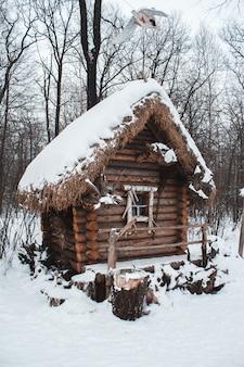 小屋は冬の雪の森の中に立っています