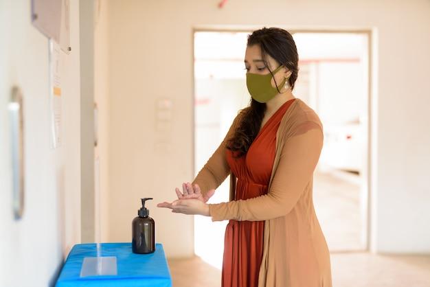手の消毒剤を使用して一緒に手をこすりながらマスクを持つ若いインド人女性