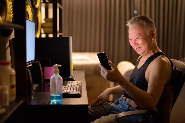 Счастливый зрелый японский человек, используя телефон во время работы из дома