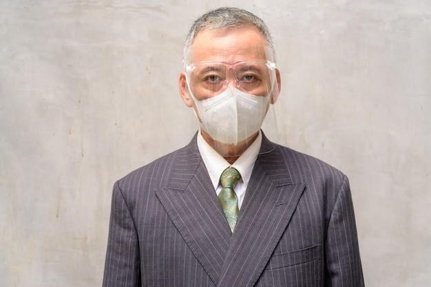 マスクと顔のシールドを持つ成熟した日本のビジネスマンの顔