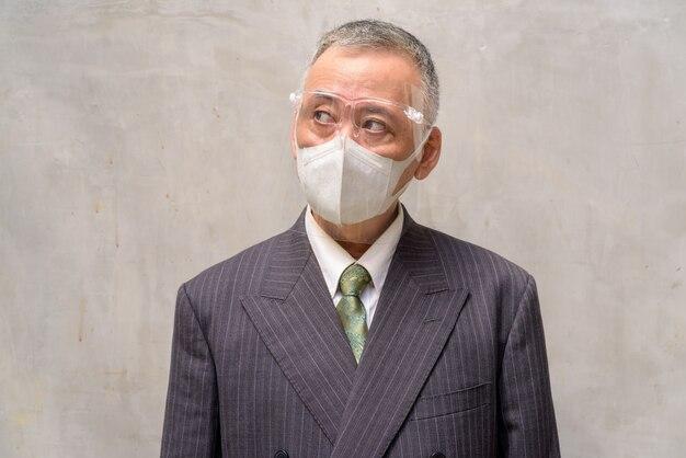 成熟した日本のビジネスマンの顔とマスクとフェイスシールド思考